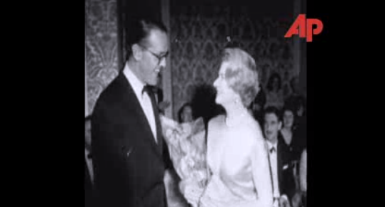 Aileen Plunkett being presented with a bouqet at the conclusion of a fashion show she hosted in Luttrellstown in 1964. Still from an AP video, whole thin available here